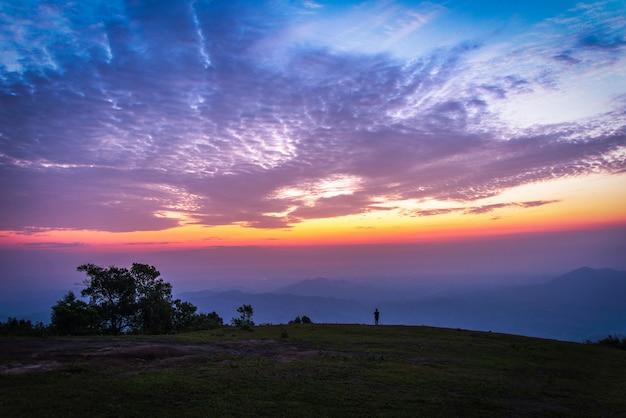 Paysage homme sur la colline ciel coucher de soleil nuages coloré ciel bleu violet