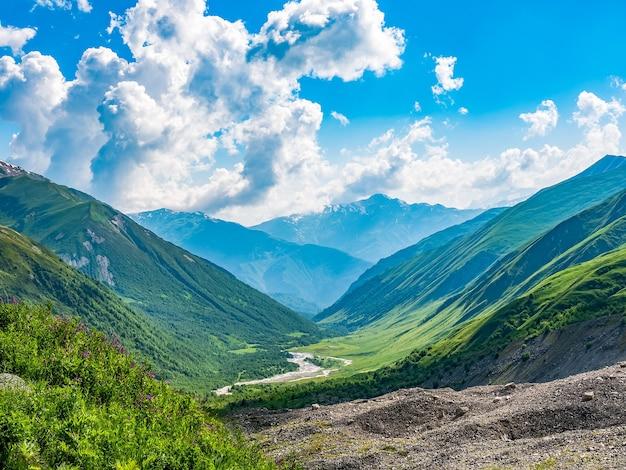 Paysage idyllique avec ciel bleu, prairies vertes fraîches, rivière et sommet de la montagne enneigée. région de svanétie, géorgie