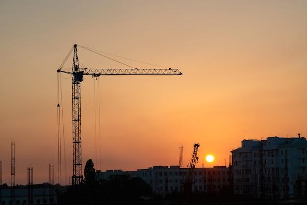Paysage industriel avec des silhouettes de grues de chantier sur fond de coucher de soleil spectaculaire