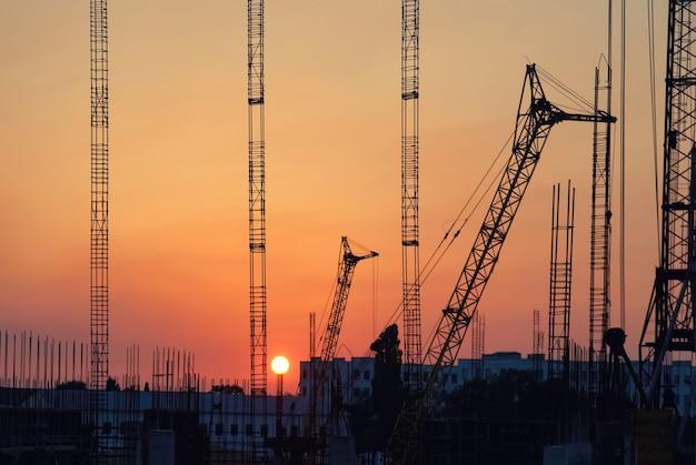 Paysage industriel avec des silhouettes de grues sur le fond du coucher du soleil