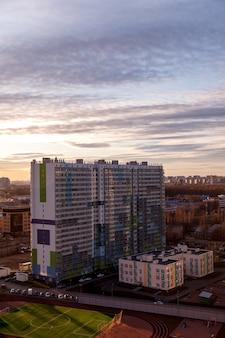 Paysage industriel urbain le soir au coucher du soleil. beau ciel bleu, bâtiments commerciaux créatifs et bâtiments résidentiels.