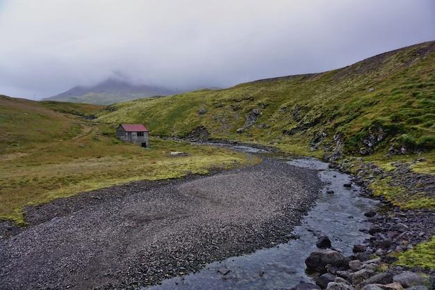Paysage islandais pendant une journée nuageuse. un chemin de gravier à proximité d'une petite maison au milieu de la campagne.