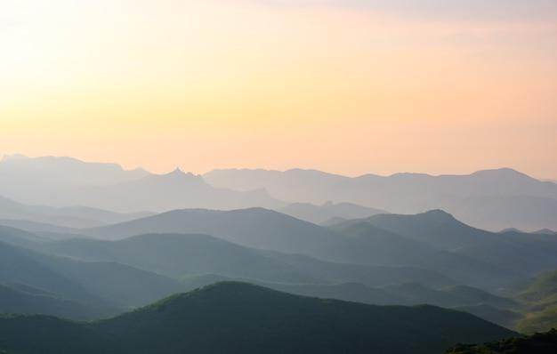 Paysage, lever du soleil dans le ciel contre les montagnes, chaînes de montagnes au lever du soleil