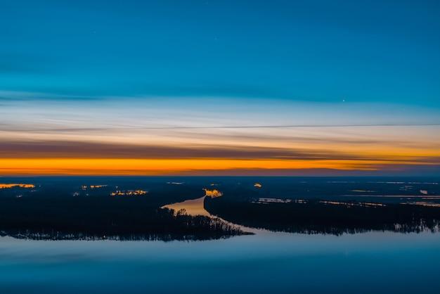 Paysage de lever du soleil avec rivière et île avec forêt sous le ciel avant l'aube