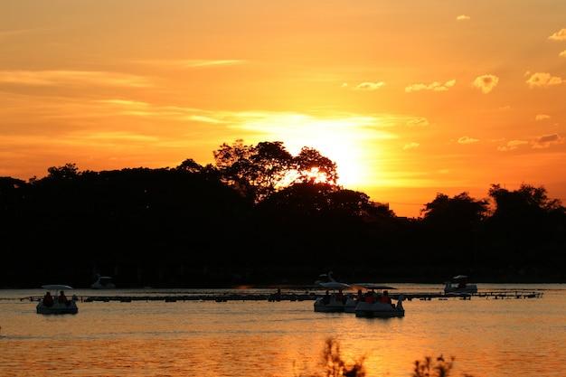 Paysage magnifique coucher de soleil dans le parc avec des gens silhouette se détendre sur un bateau
