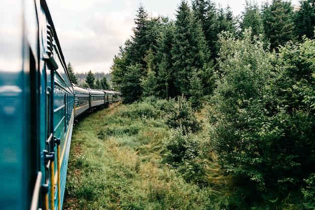 Paysage magnifique vue par la fenêtre du train à cheval entre la nature estivale avec collines, montagnes et forêts. concept de vacances et de voyage. locomotive avec wagons circulant sur une voie ferrée