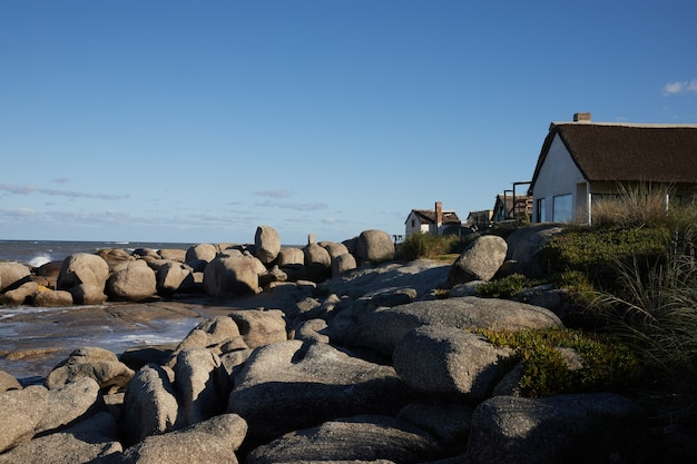 Paysage de maison sur des rochers sur la côte de l'océan, sous un ciel bleu avec des nuages.