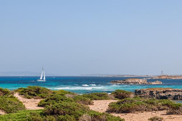 Paysage marin au large de la côte d'ibiza avec une belle mer bleue et un voilier