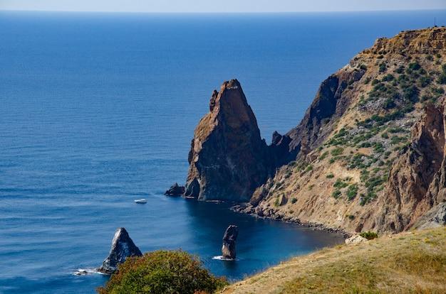 Paysage marin, ciel, montagnes, mer, grosses pierres sur la côte.