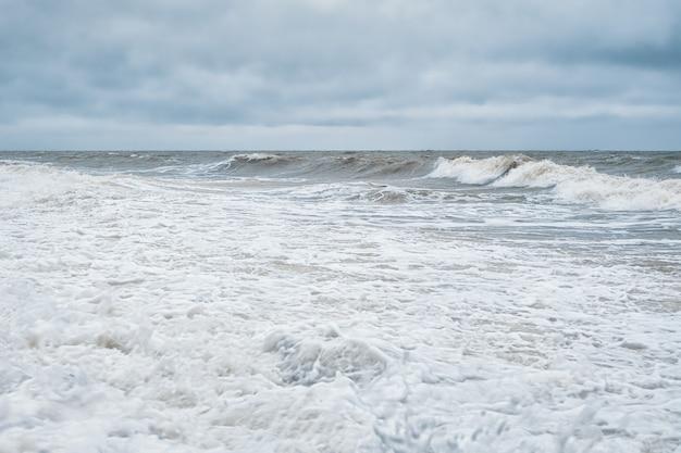 Paysage marin minimaliste dramatique avec des vagues et de la mousse blanche sur la mer blanche.