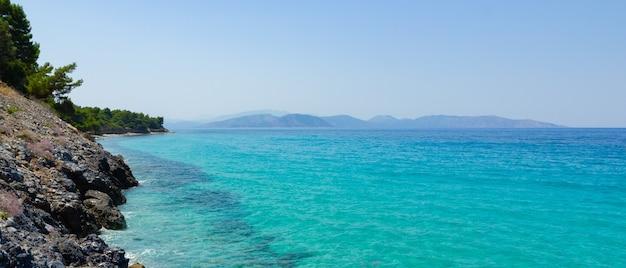 Paysage marin avec des montagnes. fleurs et arbres sur le rivage rocheux. concept de vacances d'été. copier l'espace