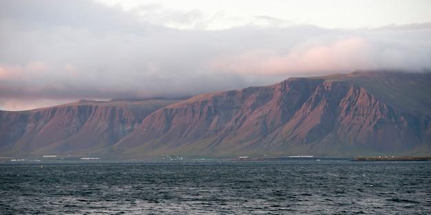 Paysage marin, océan et nuage surmonté de falaises en soirée