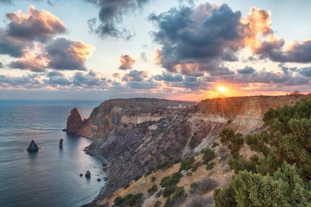 Paysage marin sur la plage de jasper au coucher du soleil, avec une falaise rocheuse éclairée par le coucher de soleil chaud. exposition longue. nuages flous de mouvement. copiez l'espace. le concept de calme silence et unité avec la nature