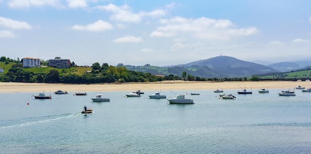 Paysage marin avec plage de sable blanc, bateaux et montagnes verdoyantes en arrière-plan