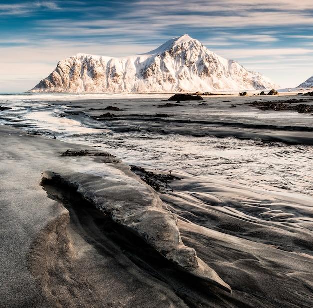Paysage marin de sillons sable avec montagne enneigée et ciel bleu dans l'océan arctique au lever du soleil