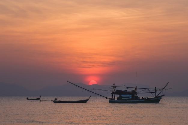 Paysage marin avec soleil et bateaux de pêche