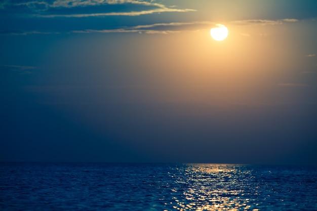 Paysage marin de la surface de la mer encore, coucher de soleil doré dans le ciel par temps clair d'été. paysages immobiles de voyages et paysages de destination