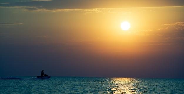 Paysage marin de la surface de la mer encore, homme équitation vélo aquatique et coucher de soleil doré dans le ciel par temps clair d'été. paysages immobiles de voyages et paysages de destination