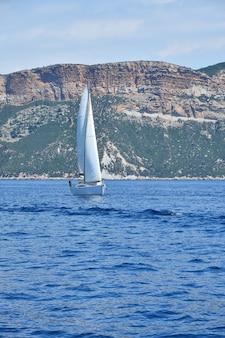 Paysage marin tranquille avec des ondulations et des vagues de l'eau de mer calme et voilier sur terre, low angle view