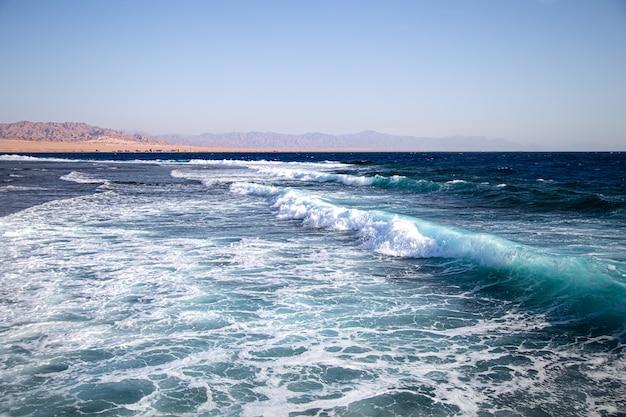 Paysage marin avec des vagues texturées et des silhouettes de montagne à l'horizon.