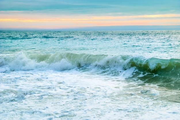 Paysage de mer avec de grosses vagues et coucher de soleil