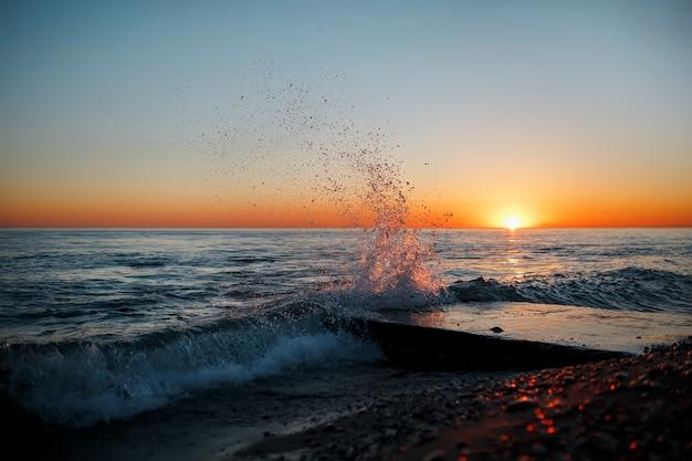 Paysage de mer avec des vagues sur la plage contre le coucher de soleil