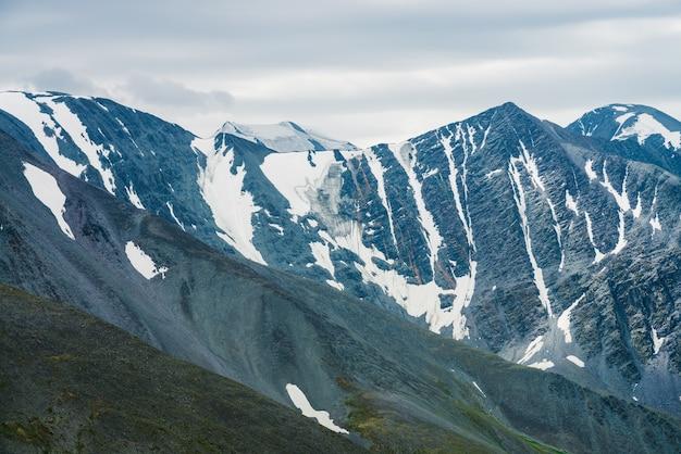 Paysage minimaliste alpin atmosphérique avec chaîne de montagnes géante et glacier massif.