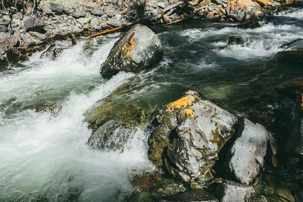 Paysage de montagne atmosphérique avec rivière de montagne turbulente parmi les rochers avec de la mousse près de la paroi rocheuse au soleil. beau paysage alpin avec des pierres moussues humides dans une puissante rivière de montagne au soleil.