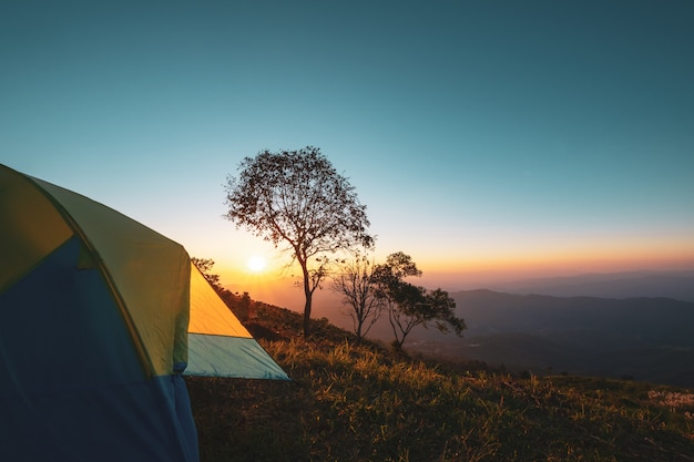 Paysage de montagne au coucher du soleil avec tente de camping.
