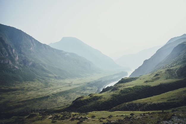 Paysage de montagne brumeux avec des collines et des rochers sur fond de grande rivière de montagne dans la brume. paysages atmosphériques avec relief montagneux et grande rivière dans une vallée vert foncé par temps de pluie. temps maussade