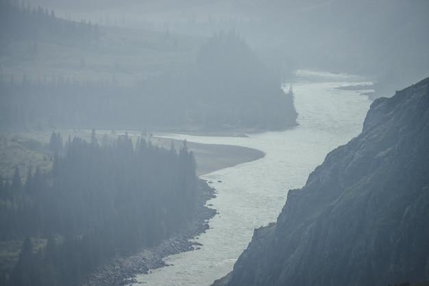Paysage de montagne brumeux avec une large rivière de montagne. paysage sombre vert foncé avec confluence de deux rivières de montagne dans la brume. vue atmosphérique sombre au confluent des grandes rivières par temps de pluie.