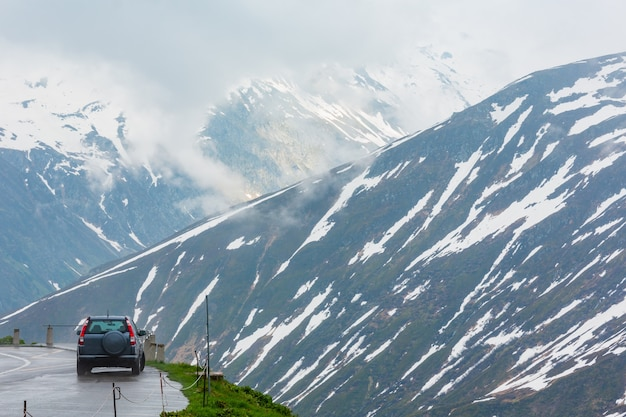 Paysage de montagne couvert nuageux au printemps (col de l'oberalp, suisse). le modèle de voiture est méconnaissable.