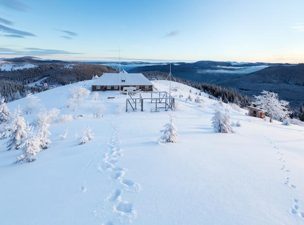 Paysage de montagne d'hiver du matin avec maison sur la crête et les traces