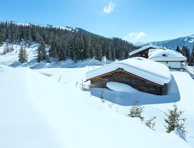 Paysage de montagne d'hiver ensoleillé et maison en bois sur la colline