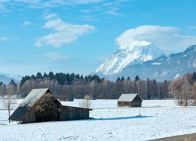 Paysage de montagne d'hiver avec des hangars en bois, autriche
