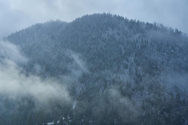 Paysage de montagne d'hiver. petite ville entre les montagnes. un nuage plane sur la ville.
