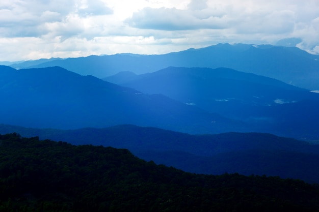 Paysage de montagne mystérieux bleu foncé dans le ciel coucher de soleil nuageux