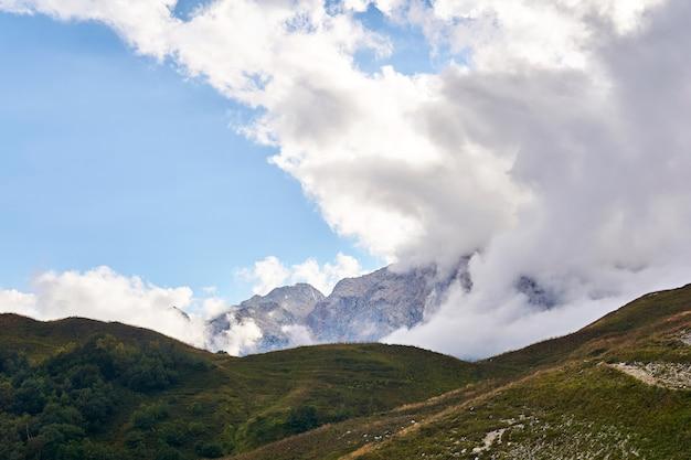 Paysage de montagne avec des nuages s'élevant de la vallée au-delà du col proche
