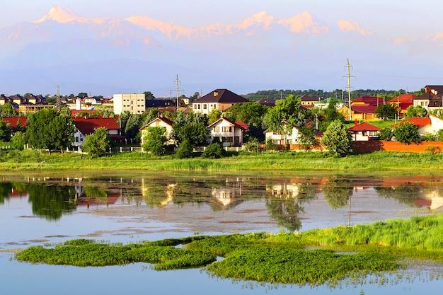 Paysage de montagne avec village au bord de la rivière