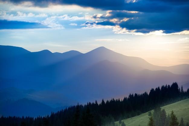 Paysage avec montagnes bleues et forêt au coucher du soleil