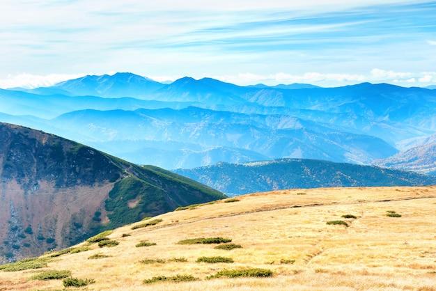 Paysage de montagnes avec champ d'herbe sèche et ciel bleu