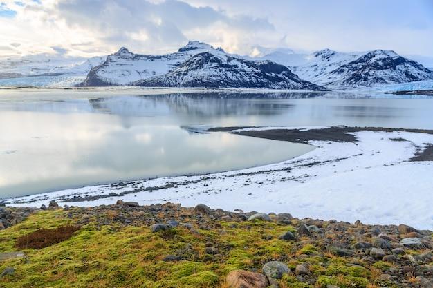 Paysage de montagnes couvertes de neige avec le premier plan de mousse verte