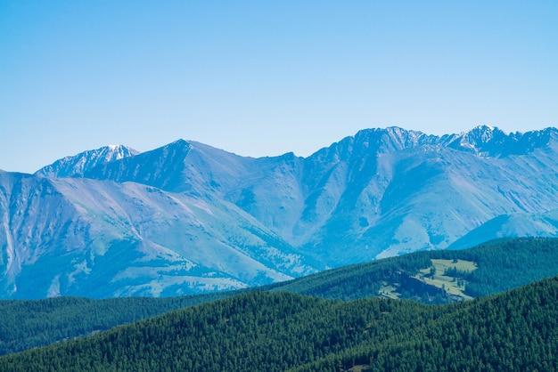 Paysage avec des montagnes géantes avec de la neige au-dessus des collines avec forêt
