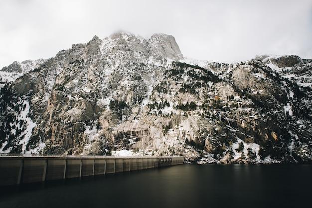 Paysage naturel d'une longue exposition à l'eau sur un marais dans les montagnes de neige en hiver