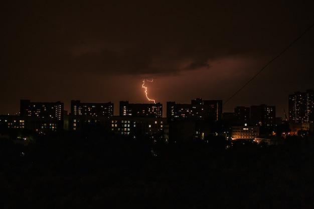 Paysage nocturne d'une grande ville avec des bâtiments et des éclairs dans les nuages temps de tempête