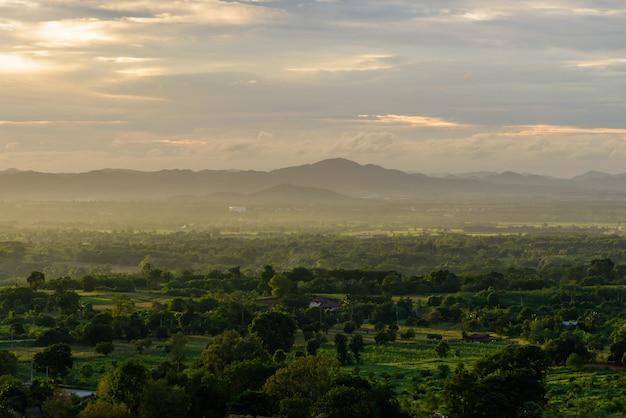 Paysage de nuages, montagne et forêt avec coucher de soleil le soir vu de dessus.