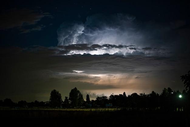 Paysage avec des nuages d'orage éclairs et nuit