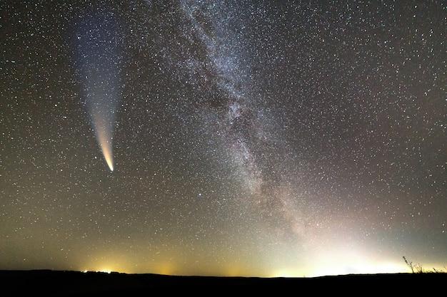 Paysage de nuit de la colline sombre avec ciel couvert d'étoiles et comète avec queue légère.