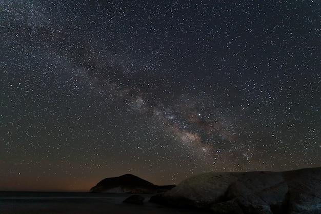 Paysage de nuit avec voie lactée depuis la plage de genoveses. parc naturel de cabo de gata. andalousie. espagne.