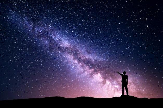 Paysage de nuit avec voie lactée et silhouette d'un homme